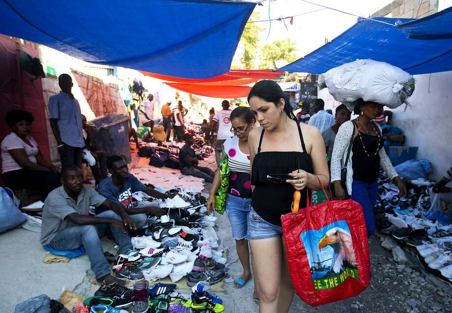 Cuban women shop at a street market in Port-au-Prince, Haiti The Cuban market in the capital city is part of a global trade, estimated to top $2 billion on bringing goods back to the island. Photo: Dieu Nalio Chery / Associated Press