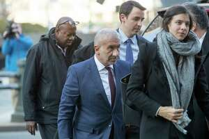 Alain Kaloyeros, center, the ex-president of the State University of New York's Polytechnic Institute, arrives for his sentencing at Manhattan Federal court, Tuesday, Dec. 11, 2018, in New York. Kaloyeros, who led the Polytechnic Institute until he resigned in October 2016, was convicted in July of conspiracy and wire fraud after prosecutors presented evidence that the bidding process for a state project was rigged to benefit a Buffalo developer and a Syracuse development company.