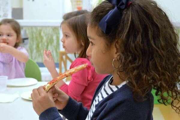 Alia Algassimi, 6, of Darien, enjoys the pizza at the Kids Night Out at the Darien YMCA, Friday, Dec. 7, 2018, in Darien, Conn.