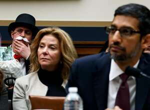 """A protester dressed as the Monopoly game character """"Rich Uncle Pennybags"""" in the audience as Sundar Pichai, Google's chief executive, testifies before the House Judiciary Committee on Capitol Hill, in Washington, Dec. 11, 2018.  Pichai was asked about whether the company's search algorithms are biased against conservatives, as well as its privacy practices and growing market power. (Ting Shen/The New York Times)"""