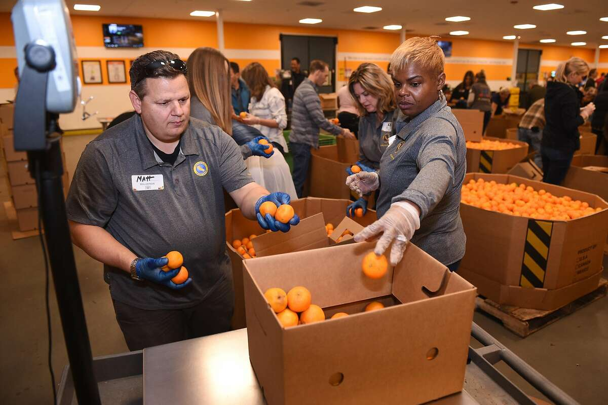 Second Harvest volunteers Matt Bunde and Lakeisha Robottom help sort and weigh boxes of oranges.