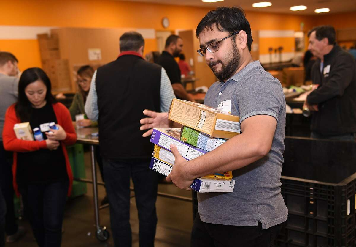 Volunteer Karthic Joshi of San Jose, an employee of Byton volunteering at Second Harvest, helps sort items at the food bank in San Jose.