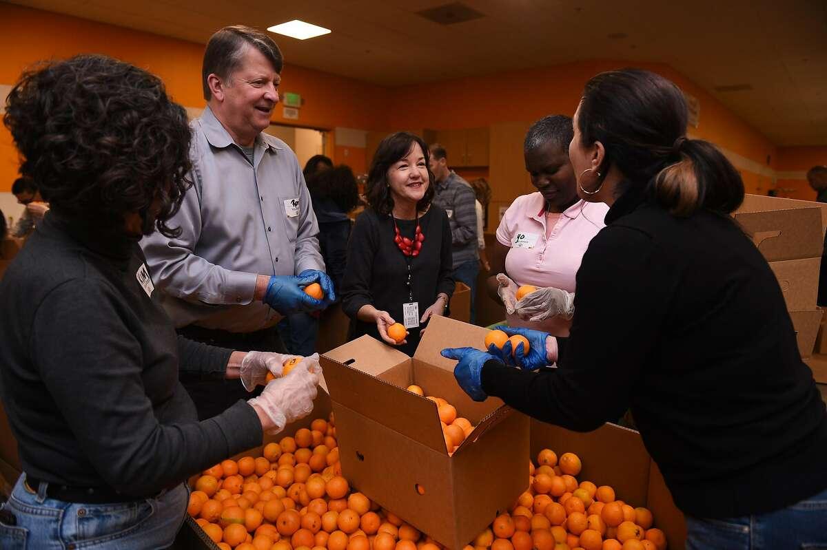 Second Harvest CEO Leslie helps volunteers Kim Eggert (left), Ron Webb, Yolanda Bealer, Ann Nervier.