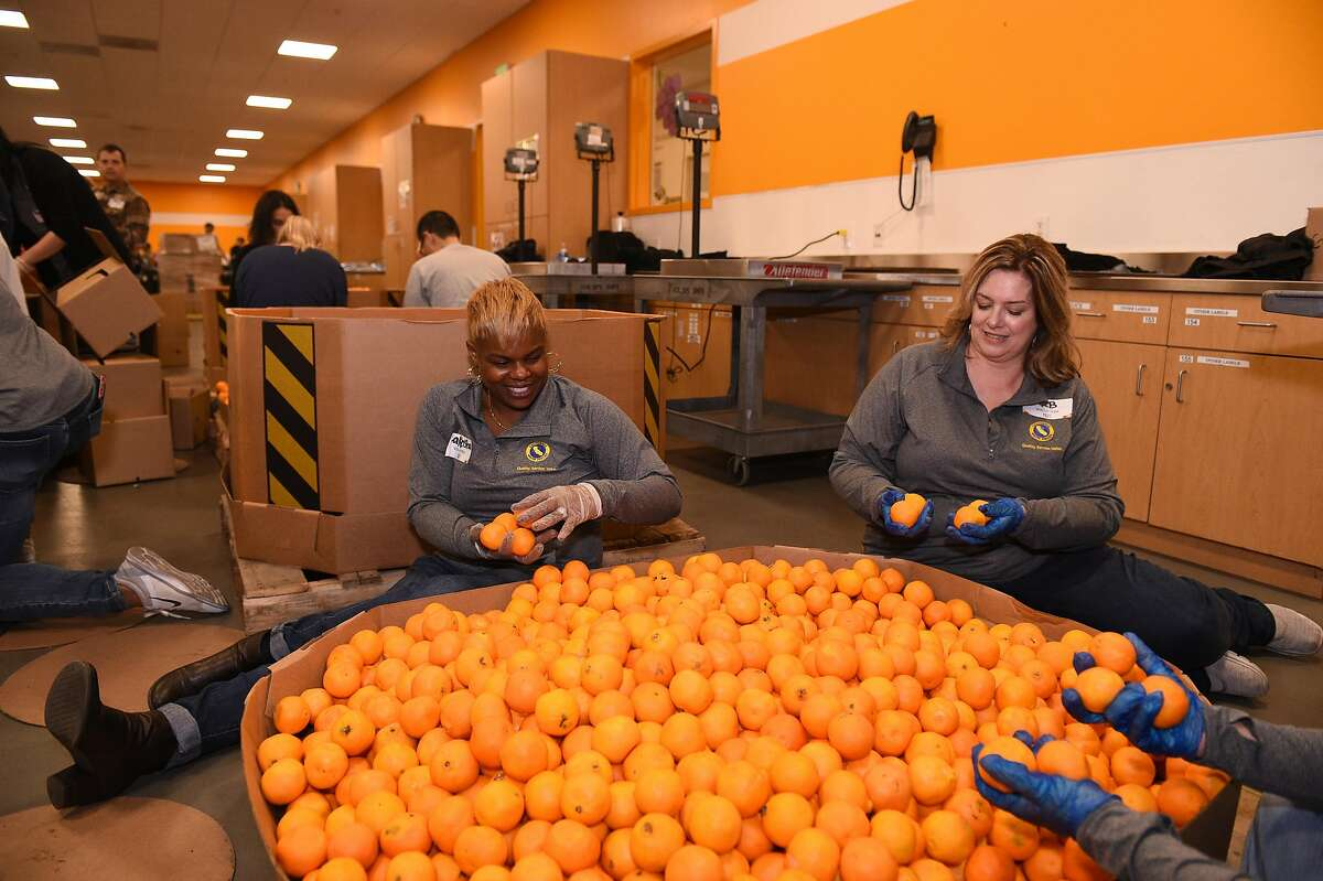Volunteers Lakeisha Robottom of Los Angeles, left, and Katrina Bray of Sacramento, both CAL Water employees, sort oranges at Second Harvest Food Bank in San Jose on Thursday December 6, 2018.