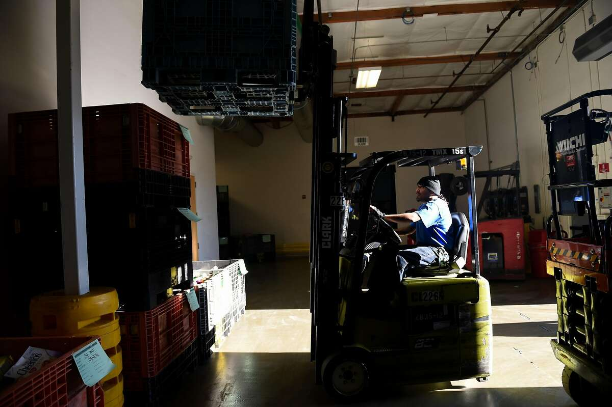 Ray Enriques of San Jose uses a fork lift to stack food which will later be distributed to those in need at Second Harvest Food Bank in San Jose on Thursday December 6, 2018.