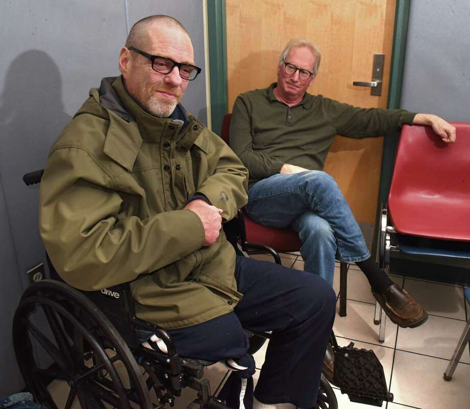 Keith Oakes, left, and old classmate Jon Maskin speak to a reporter at Capital City Rescue Mission on Tuesday, Dec. 11, 2018 in Albany, N.Y. Oakes has fallen on hard times and Maskin is raising money for his friend to get out of the shelter and get a wheelchair accessible apartment and medical care. (Lori Van Buren/Times Union) Photo: Lori Van Buren, Albany Times Union / 20045696A