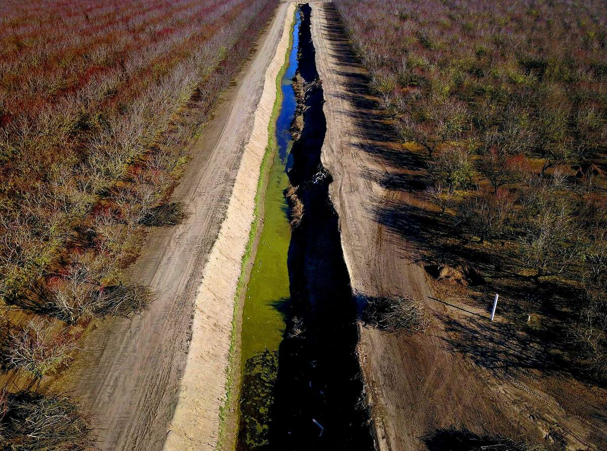An irrigation canal alongside an almond orchard off Airport Way in Modesto, Calif., on Tuesday, December 11, 2018. Sen. Dianne Feinstein is joining forces with House Republicans to try to extend a controversial law that provides more water for Central Valley farms, but with a sweetener for the environment: help with protecting California?s rivers and fish. The proposed extension of the WIIN Act, or Water Infrastructure Improvements for the Nation Act, would keep millions of federal dollars flowing for new dams and reservoirs across the West. It would also continue to allow more water to be moved from wet Northern California to the drier south. We need photos that speak to the central valley's dependance on this shipped water.