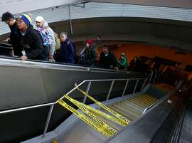 Commuters ride an elevator past a glass staircase that remains closed to the public at the main entrance Downtown Berkeley BART station in Berkeley, Calif. on Tuesday, Dec. 11, 2018. A new glass canopy and stairway opened recently after an extensive redesign but a commuter fell on the steps after recent rains created slippery conditions.