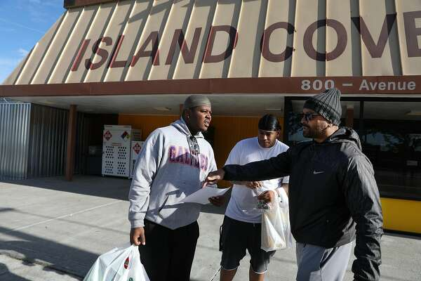 Paris Hayes (right) talks with Terrell Jeffery (left), and Terrance Oliver (partially seen center), both Treasure Island residents, in front of the Island Cove Market as he hands a flyers to encourage attendance to a City Hall meeting on Friday, Dec. 7, 2018 on Treasure Island in San Francisco.