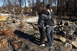 In the aftermath of the Camp Fire, Linda Haddock and her son, Jake Belculfino, embrace as they look through the remains of their house along Pentz Road in Paradise, Calif. on Thursday, December 6, 2018.