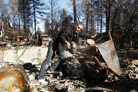 In the aftermath of the Camp Fire, Jake Belculfino, salvages items from her mother's kitchen, as his family looks through the remains of their house along Pentz Road in Paradise, Calif. on Thursday, December 6, 2018.