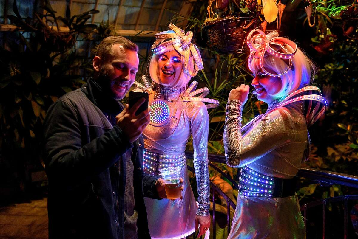 """Laurie Johnson, left, shows a phone picture to dancers Tica Bonita and Mali Jennings, who go by the performance name Circle Sphere, wear lighted costumes while participating in the new """"Night Bloom"""" installation at the San Francisco Conservatory of Flowers in San Francisco, California, on Friday, November 30, 2018."""