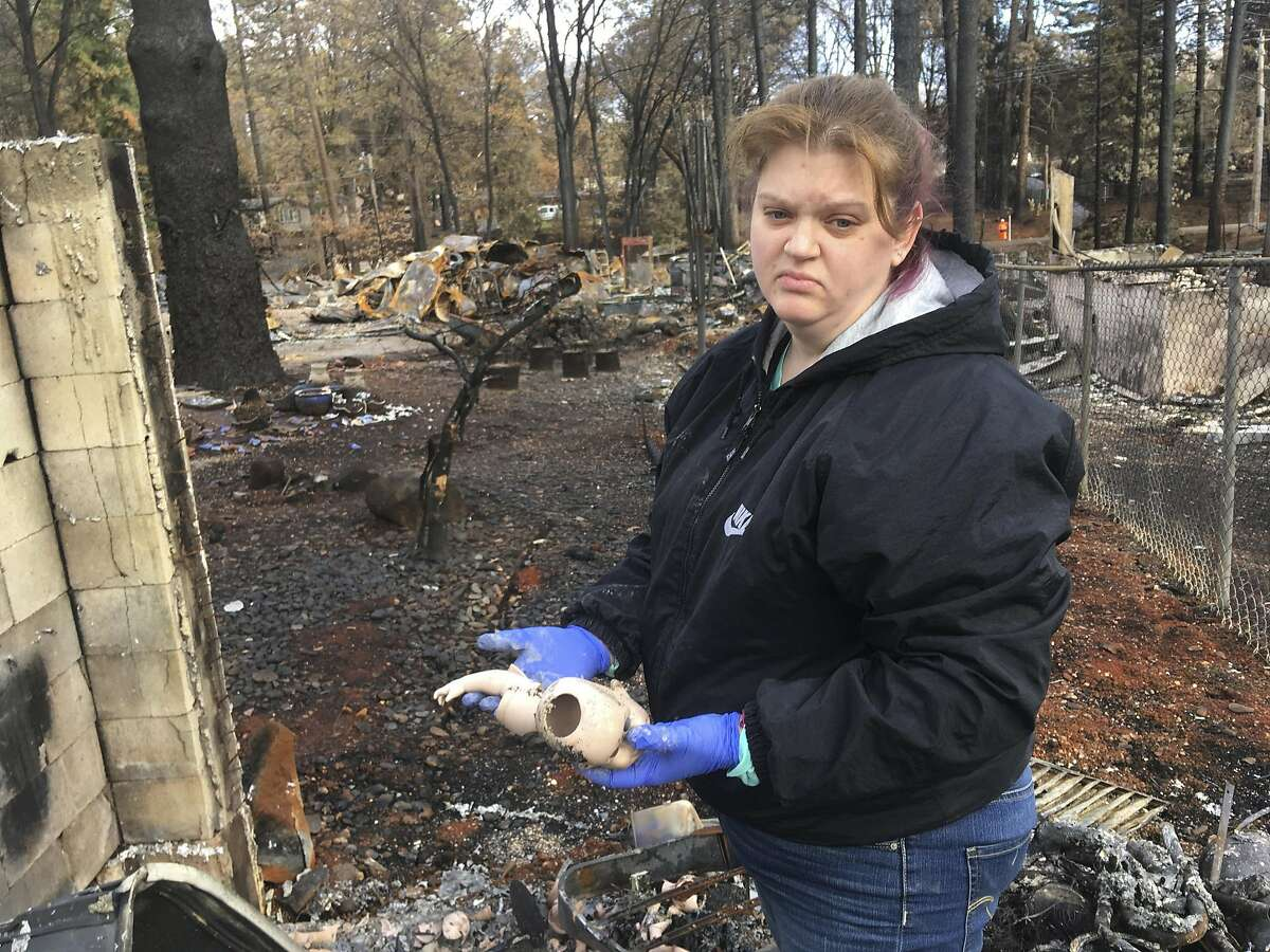 """Jennifer Christensen holds remnants of porcelain dolls that her mother gave her every Christmas that she found in the remains of her home destroyed by the Camp Fire Wednesday, Dec. 5, 2018, in Paradise, Calif. Christensen and her 2-year-old son, Avery, moved to Paradise about a year ago. Christensen is not sure of her future plans but feels so much loyalty to her town that she recently had a tattoo done on her upper arm that reads, """"Love is thicker than smoke,"""" and below that, """"Paradise Strong."""" (AP Photo/Don Thompson)"""