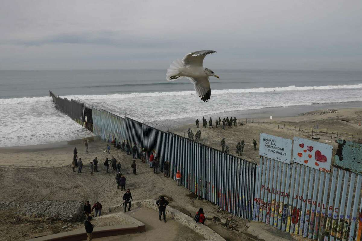 People look on from the Mexican side, left, as U.S. Border Patrol agents on the other side of the U.S. border wall in San Diego prepare for the arrival of hundreds of pro-migration protesters, seen from Tijuana, Mexico, Monday, Dec. 10, 2018. >>See how the border wall has looked over the years in the photos that follow...