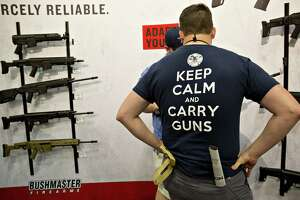 Attendees browse Bushmaster Firearms International LLC rifles at the company's booth during the National Rifle Association (NRA) annual meeting in Dallas, Texas, U.S., on Saturday, May 5, 2018. President Donald Trump delivered a strong sign of support for the National Rifle Association at its annual meeting on Friday, as gun-rights advocates regroup in the wake of the mass shooting at a Florida high school. Photographer: Daniel Acker/Bloomberg