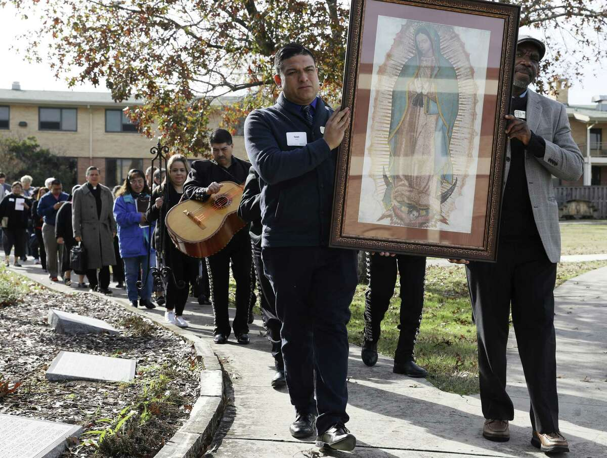 Ivan Peña, left, and Valentin Ekiaka, carry an image of the Virgin of Guadalupe, during a procession from the Mexican American Catholic College to Assumption Seminary Chapel for celebration of Mass after a panel discussion on immigration, Tuesday, Dec. 11, 2018.