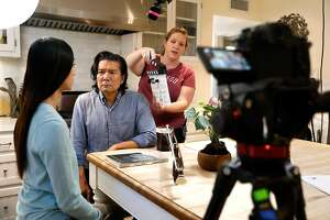 """Tiffany Chu, left and Toho Ru prepare to do a scene for the show, """"Artificial Next,"""" that streams on Twitch. At right is coordinator Rachel Williams. Ru plays the role of a scientist, Dr. Matt Lin, who is trying to make a robot named Sophie, played by Chu, more human.  Filming took place in a home in the Hollywood Hills. (Mel Melcon/Los Angeles Times/TNS)"""