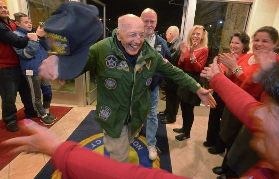 94 year old veteran of three conflicts, Carmine Pecorelli, is greeted by members of the St. Ann's Club as the Wreaths Across America caravan stops at the club for dinner Tuesday, December 10, 2018, in Norwalk, Conn. Wreaths Across America and its national network of volunteers honor veterans and lays over 700,000 memorial wreaths at 1,000 locations in the United States annually. Photo: Erik Trautmann / Hearst Connecticut Media / Norwalk Hour