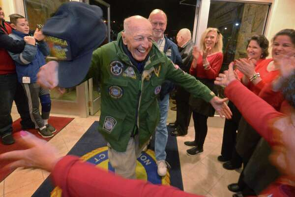 94 year old veteran of three conflicts, Carmine Pecorelli, is greeted by members of the St. Ann's Club as the Wreaths Across America caravan stops at the club for dinner Tuesday, December 10, 2018, in Norwalk, Conn. Wreaths Across America and its national network of volunteers honor veterans and lays over 700,000 memorial wreaths at 1,000 locations in the United States annually.