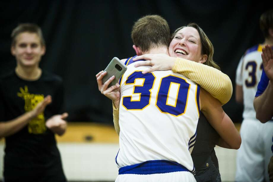 Calvary Baptist senior Mark Dickerson hugs his mother, Danelle Dickerson, after scoring the 1000th point of his high school career during a game against Lake Orion Baptist on Tuesday, Dec. 11, 2018 at Calvary Baptist Academy. (Katy Kildee/kkildee@mdn.net) Photo: (Katy Kildee/kkildee@mdn.net)