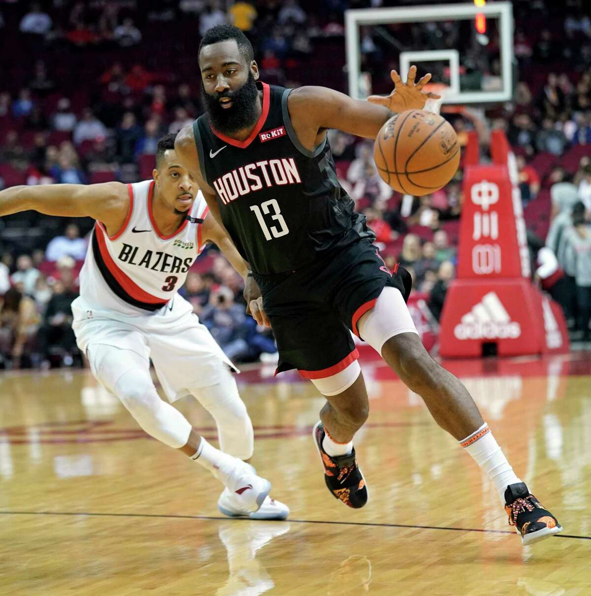 Houston Rockets' James Harden (13) drives past Portland Trail Blazers' CJ McCollum (3) during the first half of an NBA basketball game Tuesday, Dec. 11, 2018, in Houston. (AP Photo/David J. Phillip)