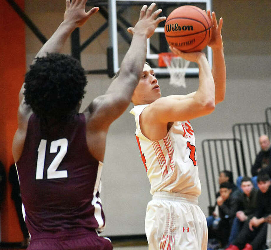 Edwardsville senior forward AJ Robertson tries to knock down a shot from the elbow during the fourth quarter against Belleville West on Tuesday inside Lucco-Jackson Gymnasium.