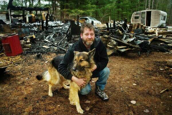 Brandon York poses for a portrait with his dog, Sadie, on Tuesday in front of what little is left of his home after it burned to the ground on Nov. 23 in Gladwin. York was able to escape the burning house with Sadie in tow. (Katy Kildee/kkildee@mdn.net)