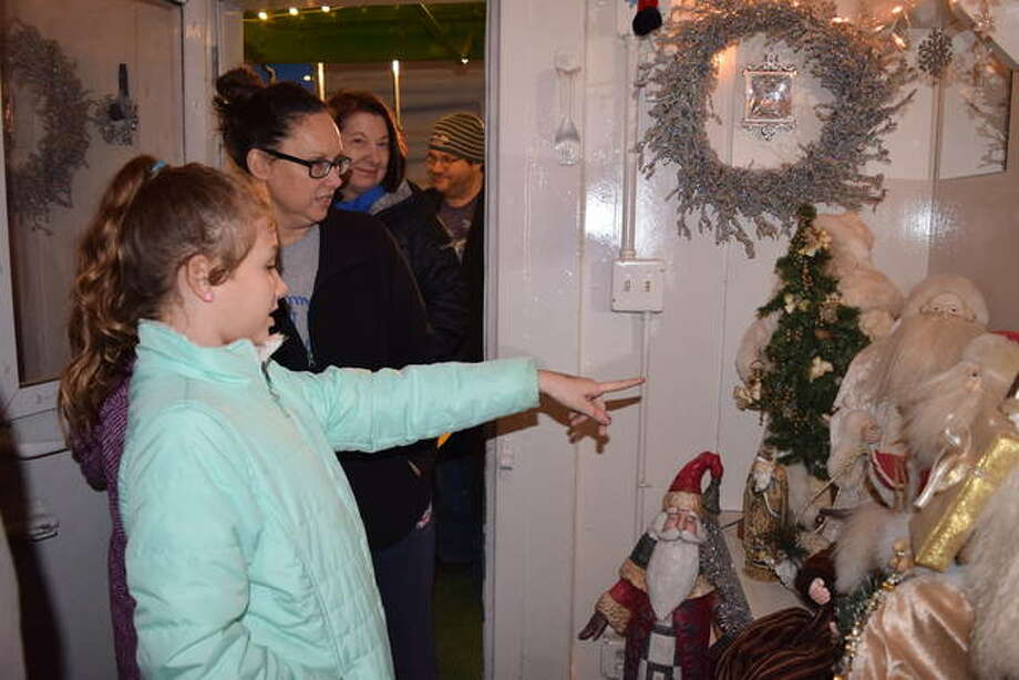 Addisyn Snyder, 9, of White Hall points out one of her favorite Santas to Terasa Snyder Tuesday on the Holiday Express. Photo: Audrey Clayton | Journal-Courier