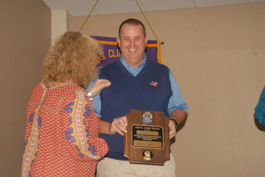 Plainview Lions Club Treasurer Kevin Carter displays his Melvin Jones Fellowship plaque while his wife Alissa attaches his Melvin Jones Fellowship pin onto his sweater. The presentation was made during Wednesday's club meeting. Photo: Courtesy Photo
