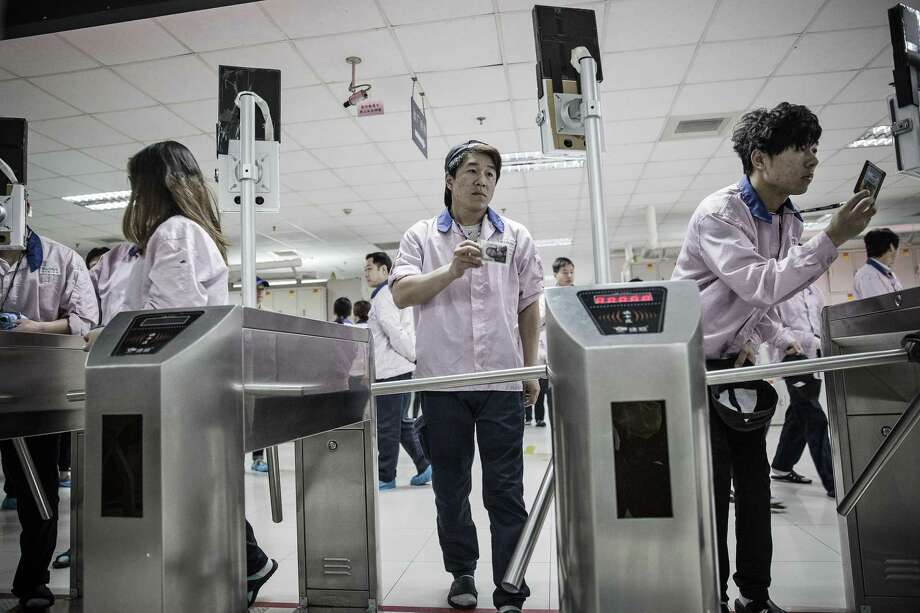 Employees look into facial recognition devices and swipe their badges to enter the assembly line area at a Pegatron factory in Shanghai, China, on April 15, 2016. Photo: Qilai Shen/Bloomberg / Bloomberg