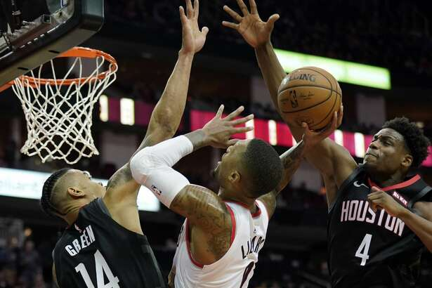 Portland Trail Blazers' Damian Lillard (0) goes up for a shot as Houston Rockets' Gerald Green (14) and Danuel House Jr. (4) defend during the second half of an NBA basketball game Tuesday, Dec. 11, 2018, in Houston. The Rockets won 111-103. (AP Photo/David J. Phillip)