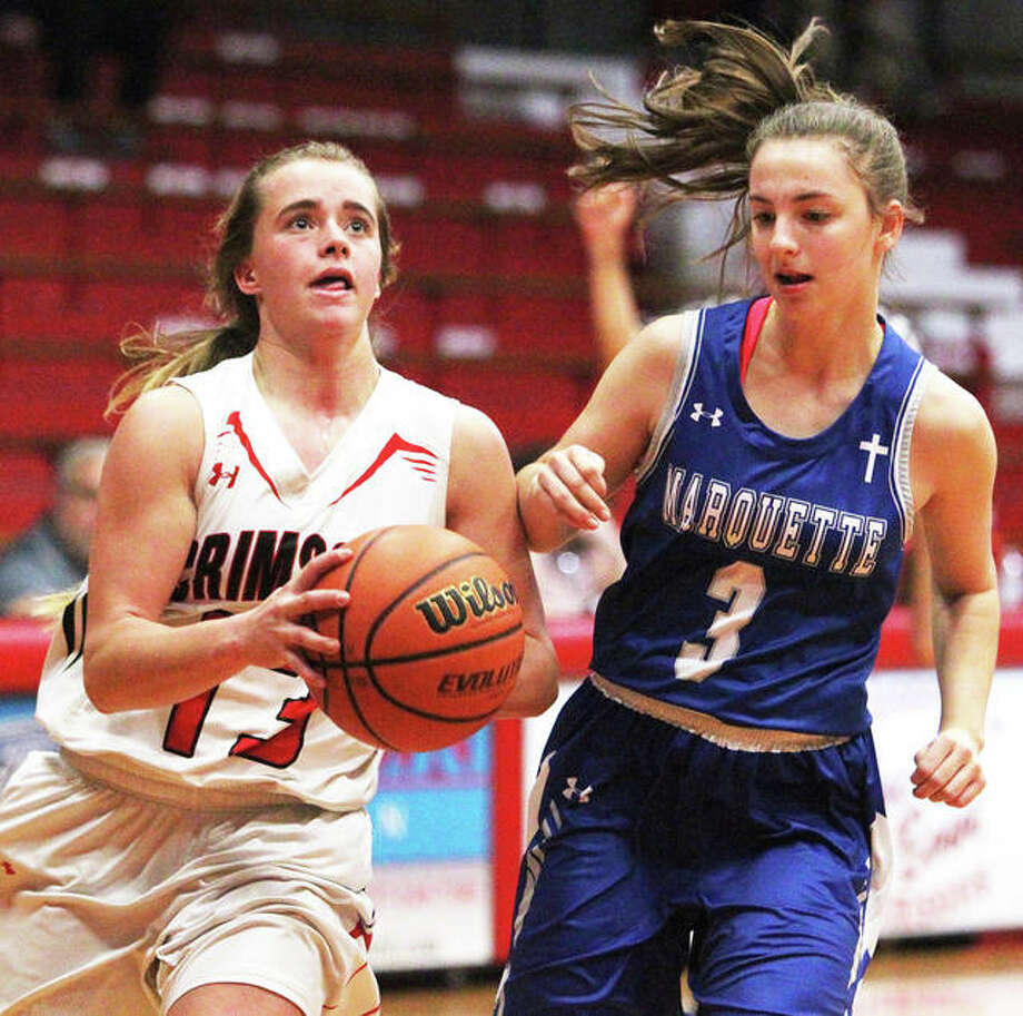 Marquette Catholic's Kamryn Fandrey (right) defends Jacksonville's Annika Robinson's drive to the basket in a Nov. 27 game in Jacksonville. The Explorers were back on the road Tuesday night at Granite City, where Fandrey scored 12 points in a Marquette victory. Photo: Dennis Mathes / Hearst Illinois