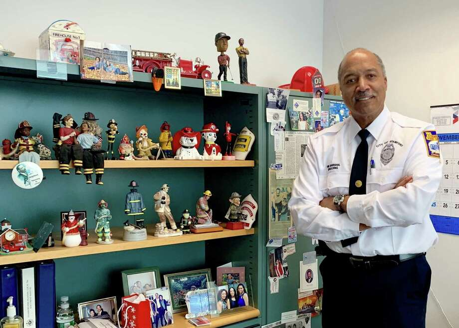Chief Fire Marshal Charles Spaulding at his office on Thursday, standing next to a book shelf and holding pictures of Stamford's first black firefighter, David Austin. Photo: James Tarzia And Robert Sollitto / Contributed