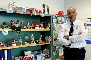 Chief Fire Marshal Charles Spaulding at his office on Thursday, standing next to a book shelf and holding pictures of Stamford's first black firefighter, David Austin.