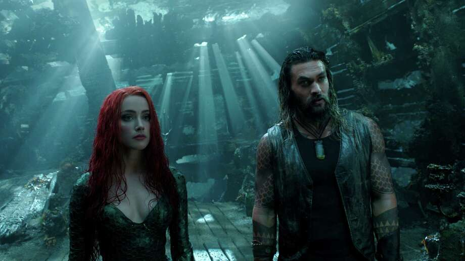 """Aquaman (Jason Momoa), right, with Mera (Amber Heard), tries to deliver sly buoyancy to the inelegantly scripted """"Aquaman,"""" according to critics. Photo: DC Comics-Warner Bros. Pictures / © 2018 Warner Bros. Entertainment Inc. and Ratpac-Dune Entertainment LLC."""