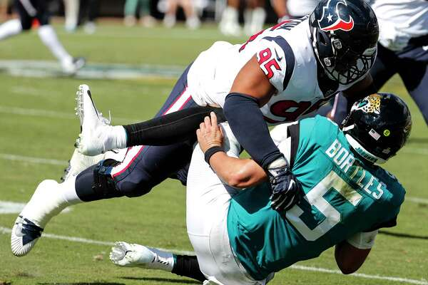 Jacksonville Jaguars quarterback Blake Bortles (5) is tackled by Houston Texans defensive end Christian Covington (95) during the second quarter of an NFL football game at TIAA Bank Field on Sunday, Oct. 21, 2018, in Jacksonville.