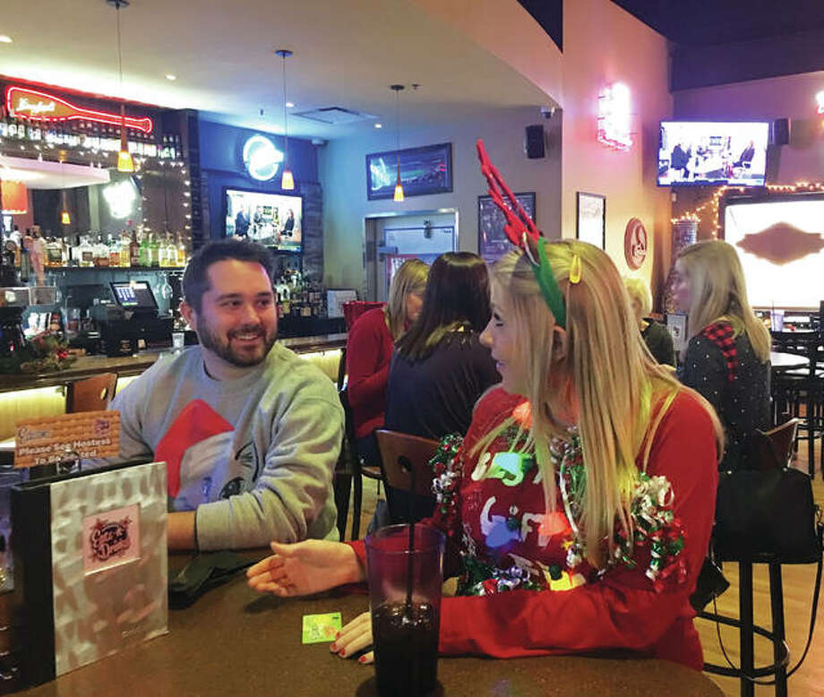 Edwardsville-based Nevco employees Dan Nettleton, 27, of Shiloh, Illinois, and Jennifer Beasley, 35, of Troy, Illinois, enjoying the company's holiday party at Edison's Entertainment Complex, for the second year in a row, in Edwardsville, Illinois.