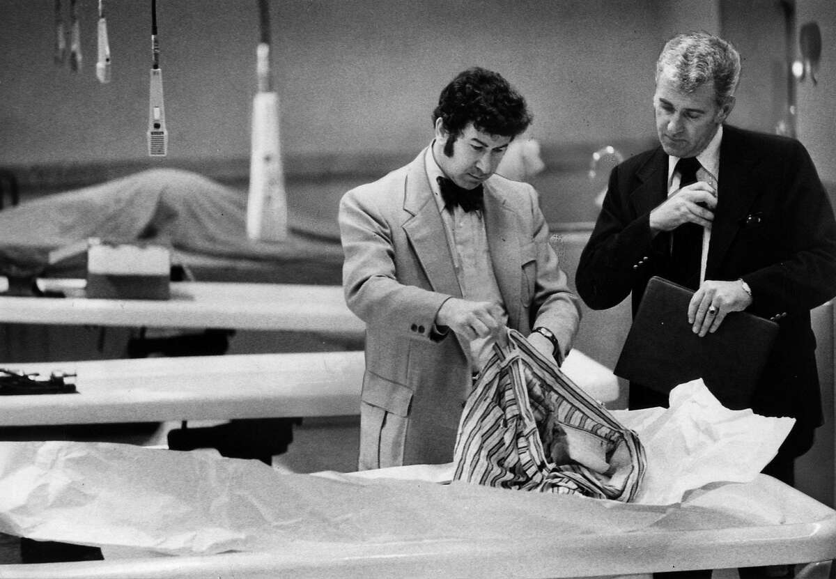 San Francisco homicide Inspectors David Toschi (left) and William Armstrong go through a homicide victim's clothes at the morgue in the Hall of Justice in San Francisco in March 1974.