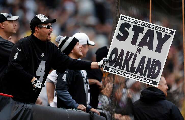 """An Oakland Raiders' fan holds a """"Stay in Oakland"""" sign during Kansas City Chiefs' 34-20 win in NFL game at O.co Coliseum in Oakland, Calif., on Sunday, December 6, 2015."""