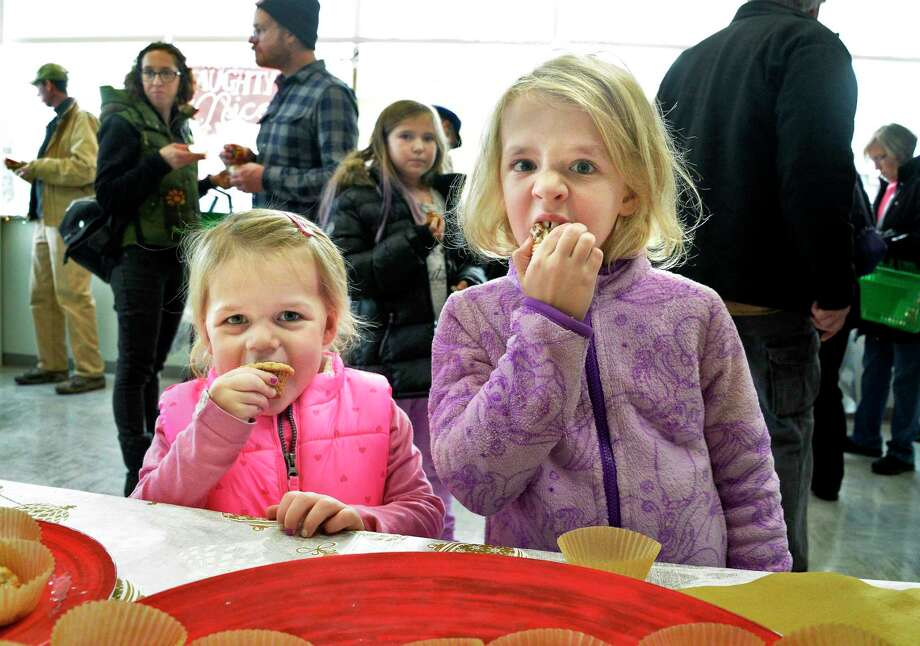 Sisters Kendall, left, and Haley Osenko of Niskayuna taste entries during the Naughty or Nice Cookie Challenge at Honest Weight Food Co-op Saturday Dec. 1, 2018 in Albany, NY.  (John Carl D'Annibale/Times Union) Photo: John Carl D'Annibale / 20045565A