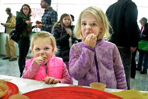 Sisters Kendall, left, and Haley Osenko of Niskayuna taste entries during the Naughty or Nice Cookie Challenge at Honest Weight Food Co-op Saturday Dec. 1, 2018 in Albany, NY.  (John Carl D'Annibale/Times Union)