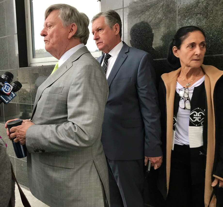 Carlos and Jemima Guimaraes against wall with attorney Rusty Hardin outside the Bob Casey Federal courthouse in Houston after they were sentenced to federal prison on Wednesday, Dec 12, 2018, for aiding in the international kidnapping of their grandson Nicholas Brann. Photo: Gabrielle Banks / Houston Chronicle