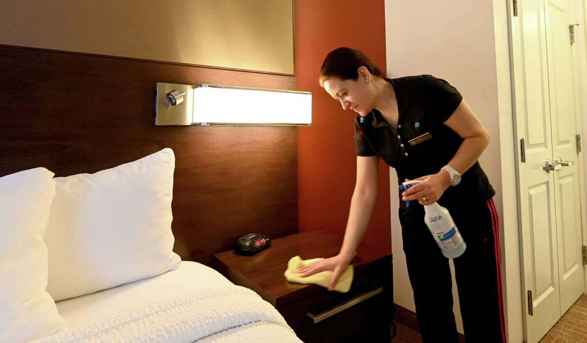 Birsen Karaca of the housekeeping department cleans end tables during her duties at the Residence Inn Albany Wednesday Dec. 11, 2018 in Albany, N.Y. (Skip Dickstein/Times Union)