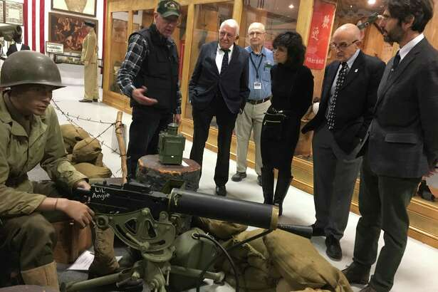 West Haven Military Museum volunteer Bill Benson shows family members of the late Edward N. Silver around the museum Wednesday.