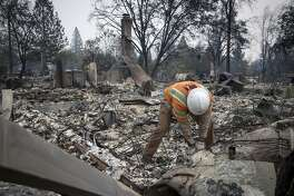 A Pacific Gas and Electric Co. worker locates a gas main line in front of a home during the Camp Fire in Paradise, California, U.S., on Tuesday, Nov. 13, 2018. The Camp Fire north of Sacramento has now killed at least 42 people, injured three firefighters and destroyed 6,500 homes, CalFire said Tuesday morning. Photographer: David Paul Morris/Bloomberg