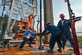 FILE: Floor hands Jose Garza, left, Jose Salinas, center, and Omar Cano make a pipe connection on Orion Drilling Co.'s Perseus drilling rig near Encinal in Webb County, Texas, U.S., on Monday, March 26, 2012. All eyes are on this weekend's G-20 summit in Argentina, where Russia's Vladimir Putin and Saudi Arabia's Mohammed bin Salman are likely to discuss how to coordinate oil policy. The nations are in talks over the timing of any reduction in supply, Reuters reported Thursday, a week before producers are due to meet in Vienna to discuss the market and a possible cut in 2019. Photographer: Eddie Seal/Bloomberg