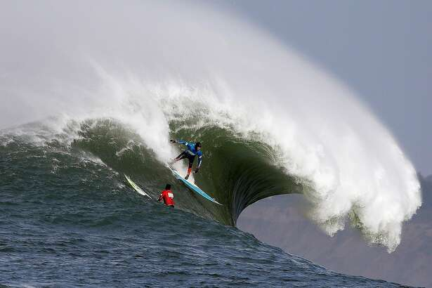 Peter Mel catches a wave as Colin Dwyer, below, is near during the second heat of the first round of the Mavericks Invitational big wave surf contest Friday, Jan. 24, 2014, in Half Moon Bay, Calif. Mel is the defending champion of the event. (AP Photo/Eric Risberg)