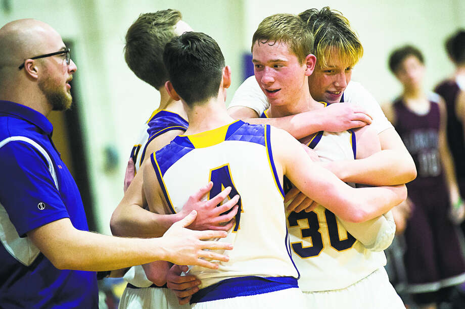 Mark Dickerson is hugged by his CBA teammates after scoring his 1,000th career point Tuesday against Lake Orion Baptist. Photo: Daily News File Photo