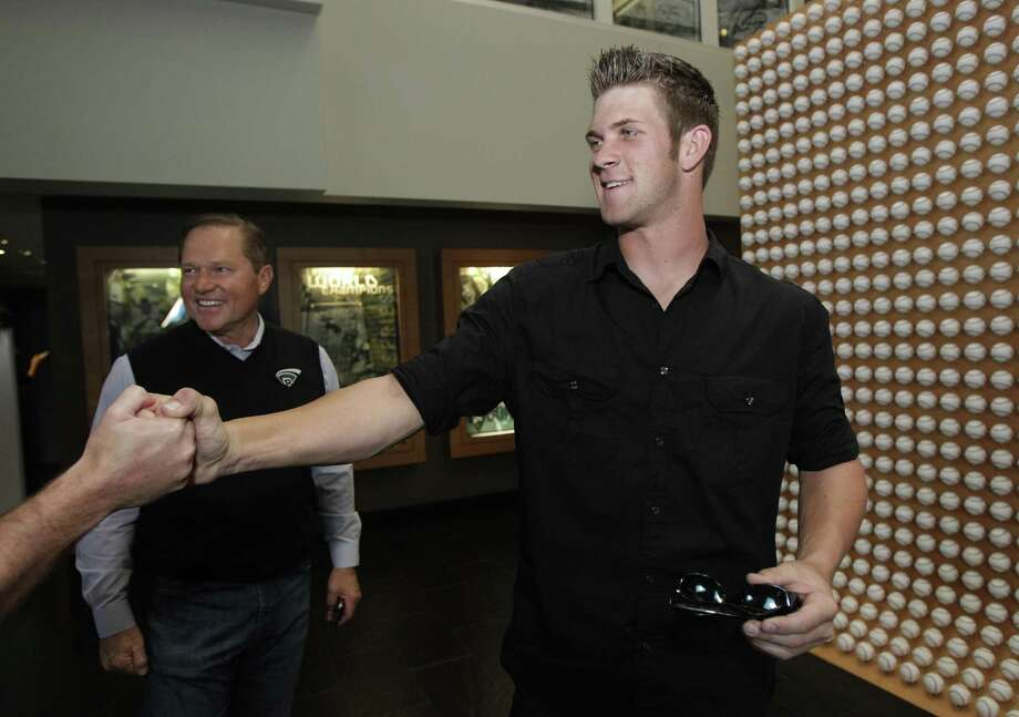 Baseball player Bryce Harper, right, shakes hands with a producer as his advisor Scott Boras watches after an interview in Newport Beach, Calif., Monday, June 7, 2010. The Washington Nationals selected junior college slugger Bryce Harper with the No. 1 overall pick in the baseball draft Monday night. (AP Photo/Jae C. Hong) Photo: Jae C. Hong / AP / AP2010