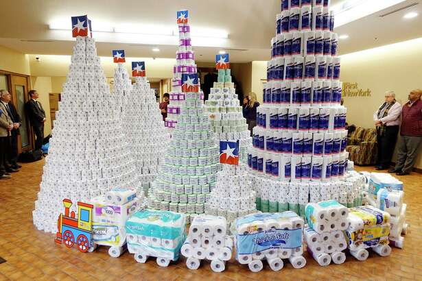 Rolls of toilet paper and paper towels are seen stacked in the shape of tress at a First New Federal Credit Union on Wednesday, Dec. 12, 2018, in Albany, N.Y. First New Federal Credit Union began collecting personal care items around Thanksgiving at branch offices and the corporate office and on Wednesday donated the 5,292 rolls of toilet paper and 2,280 rolls of paper towels to Catholic Charities of the Diocese of Albany. Sister Betsy Van Deusen, director of community partnerships at Catholic Charities, said that most people are not aware that those in need can not use food stamps to buy personal care items. Catholic Charities will distribute the items through their food pantries in Albany and Rensselaer Counties. Last year the food pantries server 15,000 people. (Paul Buckowski/Times Union)